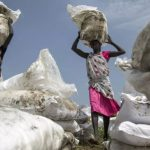 Women carry sacks of food airdropped by the World Food Programme and distributed by the NGO Oxfam in Padding, near Lankien, Jonglei, South Sudan in 2017. Click to enlarge.