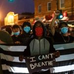"""Protestors with a sign saying""""I can't breathe"""" … while wearing masks that affect their breathing. Symbolic."""