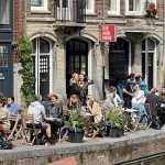While 120 countries in the world ordered citizens to wear masks in public places to prevent the spread of Covid-19, the Dutch are doing things differently. Pictured, people enjoying a drink in Amsterdam. Click to enlarge