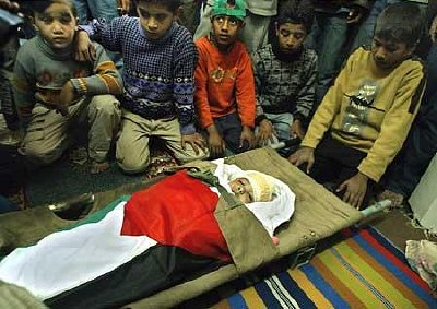 Palestinian boys gather around the body of Rahma Abu Shamas, the 3-year-old hit in the head by Israeli gunfire while she was inside her home. Photo: MAHMUD HAMS