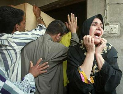 An Iraqi woman grieves as five coffins are brought into their former home in the Baghdad suburb of Zaafaraniya after an explosion, April 26, 2003. Many Iraqi civilians were believed killed on Saturday when an arms dump exploded outside Baghdad, sending rockets scything into nearby housing, and residents blamed U.S. troops for the tragedy. REUTERS/Chris Helgren