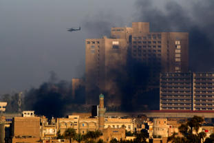 A U.S. Apache helicopter hovers over the smoke above Baghdad's restive Haifa Street on Wednesday. SABAH ARAR: AFP/GETTY IMAGES