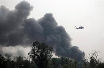 A helicopter flies past a column of smoke rising from the Green Zone