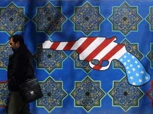 A man walks past a mural near the old US embassy in Tehran