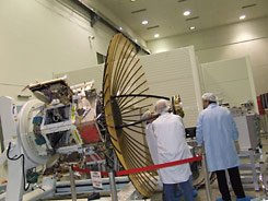 Engineers examine the satellite prior to launch