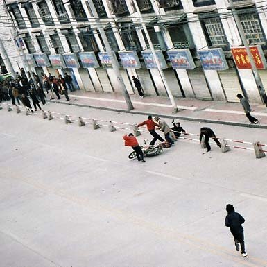 Tibetans attack a Chinese motorcyclist in Lhasa.