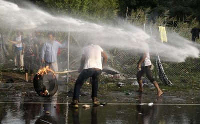 Migrants challenging Hungary's new border fence.
