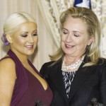 Hillary Clinton admires Christine Aguilera's breasts. Clinton is rumoured to be an active bisexual. Click to enlarge