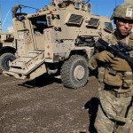 US army soldiers stand next to military vehicles in the town of Bartella, east of Mosul, Iraq. Click to enlarge