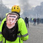 """A Yellow Vest protester wearing a mask depicting the French President on which is written the word 'psycho' looks at fellow protesters in Paris on March 16, 2019, during the 18th consecutive Saturday of demonstrations called by the 'Yellow Vest' (gilets jaunes) movement. - Demonstrators hit French city streets again on March 16, for a 18th consecutive week of nationwide protest against the French President's policies and his top-down style of governing, high cost of living, government tax reforms and for more """"social and economic justice."""" (Photo by Alain JOCARD / AFP)"""