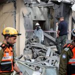 Israeli police and soldiers examine the ruins of a house hit by rockets north of Tel Aviv. Click to enlarge
