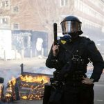 A Danish police officer stands guard during the riots at Norrebro in Copenhagen. Click to enlarge
