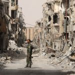 A fighter from Syrian Democratic Forces (SDF) stands next to debris of damaged buildings in Raqqa, Syria September 25, 2017. REUTERS/Rodi Said