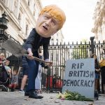 A person wearing a Boris Johnson 'head' digs a grave at the foot of a tombstone during a protest organised by Avaaz and Best for Britain, outside Downing Street in London. (Photo by Stefan Rousseau/PA Images via Getty Images)