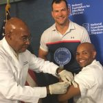Surgeon General Dr. Jerome Adams receives a flu shot as Cleveland Browns offensive tackle Joe Thomas looks on